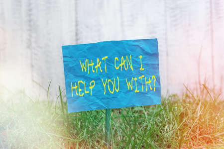 Text sign showing What Can I Help You With Question. Business photo showcasing to make it possible for someone to do Plain empty paper attached to a stick and placed in the green grassy land