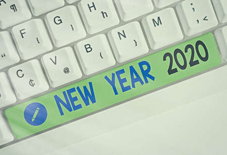 Word writing text New Year 2020. Business photo showcasing Greeting Celebrating Holiday Fresh Start Best wishes Different colored keyboard key with accessories arranged on empty copy space