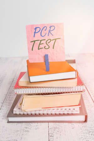Word writing text Pcr Test. Business photo showcasing qualitative detection of viral genome within the short seqeunce of DNA pile stacked books notebook pin clothespin colored reminder white wooden