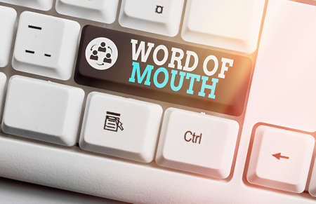 Writing note showing Word Of Mouth. Business concept for information that is transmitted without being written down Colored keyboard key with accessories arranged on empty copy space
