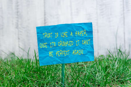 Text sign showing Trust Is Like A Paper, Once It is Crumbled It Cant Be Perfect Again. Business photo showcasing trust Plain empty paper attached to a stick and placed in the green grassy land Foto de archivo