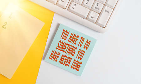 Handwriting text You Have To Do Something You Have Never Done. Conceptual photo to change your mindset Empty blank paper with copy space and pc keyboard above orange background table