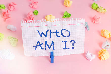 Conceptual hand writing showing Who Am I Question. Concept meaning asking about selfidentity or an individualal purpose in life Colored crumpled papers empty reminder pink floor clothespin