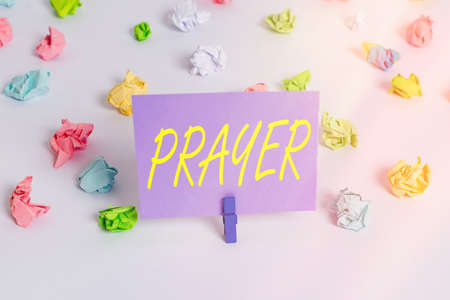 Handwriting text writing Prayer. Conceptual photo solemn request for help or expression of thanks addressed to God Colored crumpled papers empty reminder white floor background clothespin