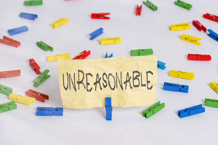 Handwriting text writing Unreasonable. Conceptual photo beyond right or acceptability boundaries or behaving in a way Colored clothespin papers empty reminder white floor background office