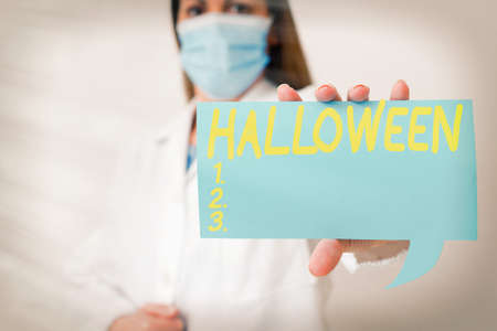 Conceptual hand writing showing Halloween. Concept meaning October 31 observed especially with dressing up in disguise Laboratory technician featuring paper accessories smartphone 版權商用圖片