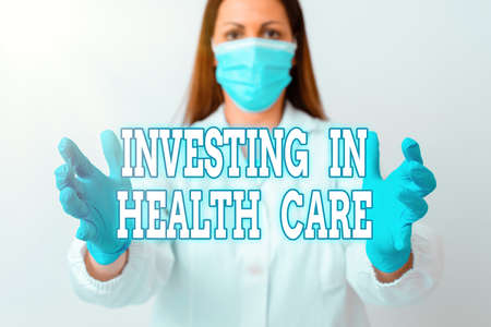 Text sign showing Investing In Health Care. Business photo showcasing put money on maintenance or improvement of health Laboratory technician featuring empty sticker paper accessories smartphone