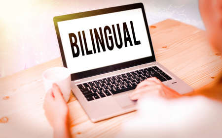 Conceptual hand writing showing Bilingual. Concept meaning using or able to use two languages especially with equal fluency Modern gadgets white screen under colorful bokeh background Imagens
