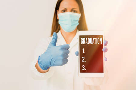 Conceptual hand writing showing Graduation. Concept meaning the award or acceptance of an academic degree or diploma Laboratory technician featuring paper accessories smartphone
