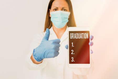 显示毕业的概念性手写。概念意味着学位或文凭实验室技术人员的奖励或接受纸质配件智能手机