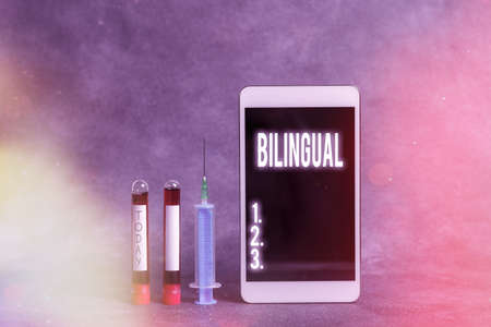 Text sign showing Bilingual. Business photo showcasing using or able to use two languages especially with equal fluency Extracted blood sample vial with medical accessories ready for examination