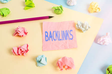 Conceptual hand writing showing Backlinks. Concept meaning links from one website to a page on another website or page Colored crumpled papers empty reminder blue yellow clothespin