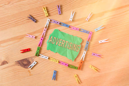 Conceptual hand writing showing Advertising. Concept meaning action of calling attention of the public by paid announcements Colored crumpled papers wooden floor background clothespin
