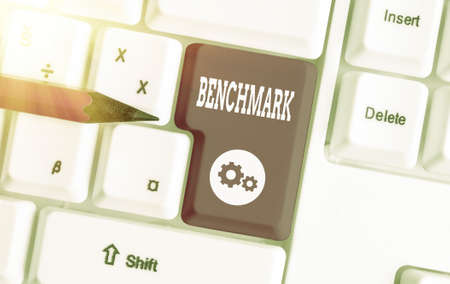 Writing note showing Benchmark. Business concept for something that serves as a standard by which others may be measured Colored keyboard key with accessories arranged on empty copy space