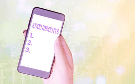 Writing note showing Amendments. Business concept for process of amending a law or document by parliamentary. Modern gadgets white screen under colorful bokeh background