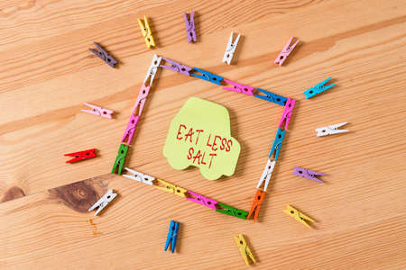 Text sign showing Eat Less Salt. Business photo text reducing the sodium intake on the food and beverages Colored clothespin papers empty reminder wooden floor background office