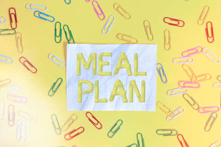 Word writing text Meal Plan. Business photo showcasing act of taking time to plan any number of meals for the week Flat lay above empty paper with copy space and colored paper clips Stok Fotoğraf
