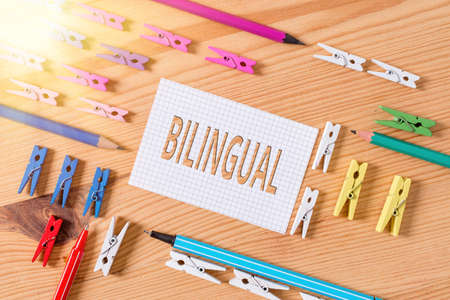 Conceptual hand writing showing Bilingual. Concept meaning using or able to use two languages especially with equal fluency Colored crumpled papers wooden floor background clothespin