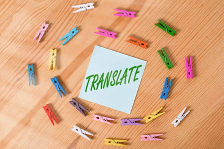 Writing note showing Translate. Business concept for bear, remove, or change from one place, state, form, or appearance Colored clothespin papers empty reminder wooden floor background office Foto de archivo