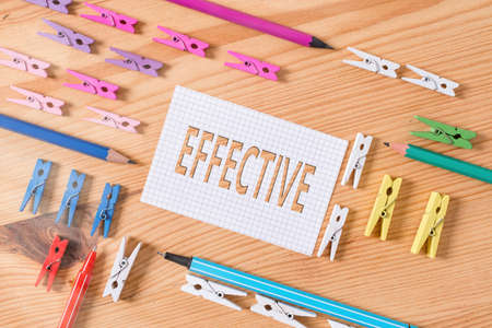 Conceptual hand writing showing Effective. Concept meaning equal to the rate of simple interest that yields the same amount Colored crumpled papers wooden floor background clothespin