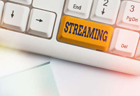 Text sign showing Streaming. Business photo text process, or an instance of streaming data or accessing data Different colored keyboard key with accessories arranged on empty copy space