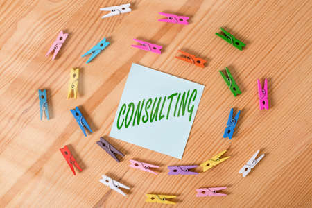 Writing note showing Consulting. Business concept for business of giving expert advice typically in business matters Colored clothespin papers empty reminder wooden floor background office