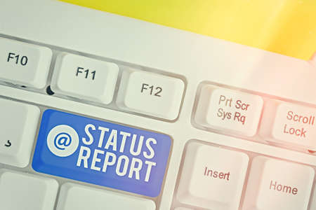 Writing note showing Status Report. Business concept for summarizes the particular situation as of a stated period Colored keyboard key with accessories arranged on empty copy space