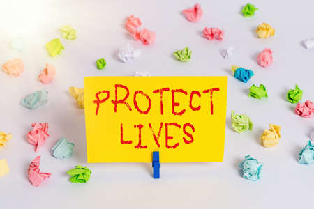 Handwriting text Protect Lives. Conceptual photo to cover or shield from exposure injury damage or destruction Colored crumpled papers empty reminder white floor background clothespin