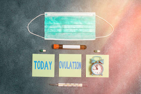 Handwriting text writing Ovulation. Conceptual photo the discharge of a mature ovum from the ovary for impregnation Extracted blood sample vial with medical accessories ready for examination