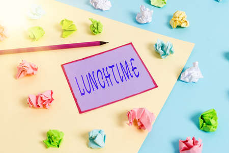 Conceptual hand writing showing Lunchtime. Concept meaning the time at which lunch is usually eaten : NOON, 12 o clock Colored crumpled papers empty reminder blue yellow clothespin