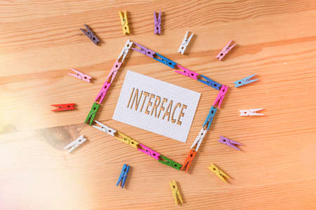 Writing note showing Interface. Business concept for the means by which interaction or communication is achieved Colored clothespin papers empty reminder wooden floor background office Stock Photo