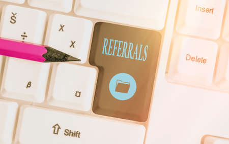 Text sign showing Referrals. Business photo showcasing act, action, or an instance of referring to someone for work Different colored keyboard key with accessories arranged on empty copy space