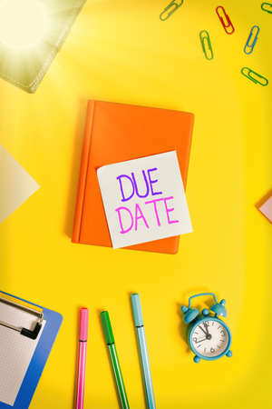 Handwriting text writing Due Date. Conceptual photo the day or date by which something is supposed to be done or paid Flat lay above table with copy space paper clips clock and pencils