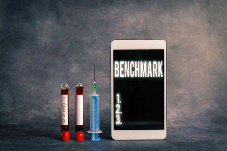 Text sign showing Benchmark. Business photo showcasing something that serves as a standard by which others may be measured Extracted blood sample vial with medical accessories ready for examination