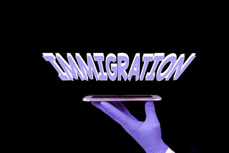Writing note showing Immigration. Business concept for the action of coming to live permanently in a foreign country Displaying Sticker Paper Accessories With Medical Gloves On Banco de Imagens