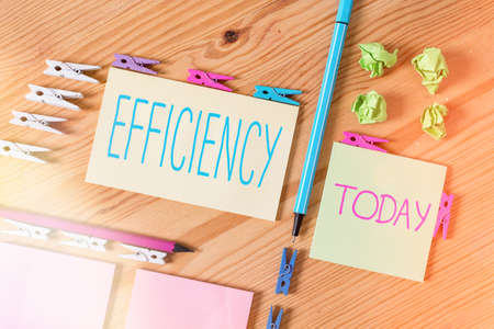 Handwriting text writing Efficiency. Conceptual photo ability to avoid wasting materials, efforts, in doing something Colored clothespin papers empty reminder wooden floor background office