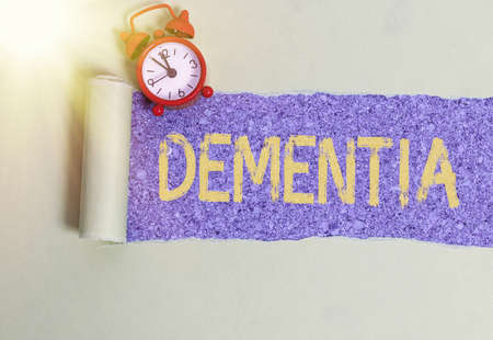 Handwriting text writing Dementia. Conceptual photo usually, a progressive condition marked by multiple deficits Rolled ripped torn cardboard placed above a wooden classic table backdrop