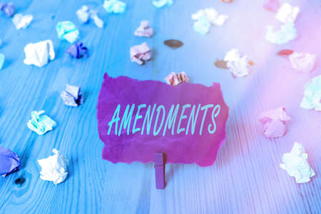 Text sign showing Amendments. Business photo text process of amending a law or document by parliamentary. Colored crumpled rectangle shaped reminder paper light blue background