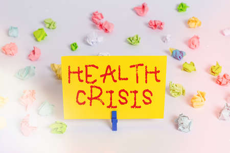 Handwriting text Health Crisis. Conceptual photo fitness problem that affects in more geographic areas Colored crumpled papers empty reminder white floor background clothespin
