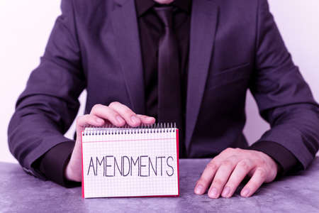 Conceptual hand writing showing Amendments. Concept meaning process of amending a law or document by parliamentary. Model displaying different color notepad mock-up for writing idea