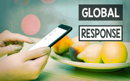 Handwriting text Global Response. Conceptual photo indicates the behaviour of material away from impact point Modern gadgets with white display screen under colorful bokeh background