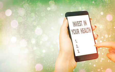 Text sign showing Invest In Your Health. Business photo text put money on maintenance or improvement of your health Modern gadgets with white display screen under colorful bokeh background