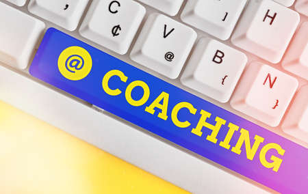 Writing note showing Coaching. Business concept for to instruct, direct, or prompt as a coach to subordinates Colored keyboard key with accessories arranged on empty copy space