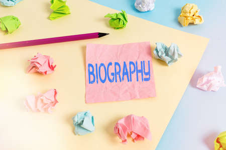 Conceptual hand writing showing Biography. Concept meaning an account of the life of something such as an animal, a coin, etc. Colored crumpled papers empty reminder blue yellow clothespin Standard-Bild