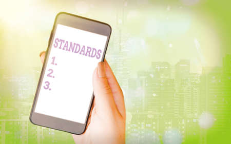 Writing note showing Standards. Business concept for something established by authority, custom, or general consent Modern gadgets white screen under colorful bokeh background