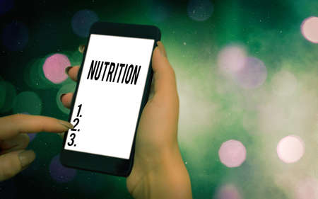 Conceptual hand writing showing Nutrition. Concept meaning act or process of nourishing or being nourished by nutrients Modern gadgets white screen under colorful bokeh background