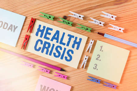 Word writing text Health Crisis. Business photo showcasing fitness problem that affects in more geographic areas Colored clothespin papers empty reminder wooden floor background office