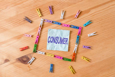 Handwriting text Consumer. Conceptual photo one that utilizes economic goods that are sold by manufacturers Colored clothespin papers empty reminder wooden floor background office
