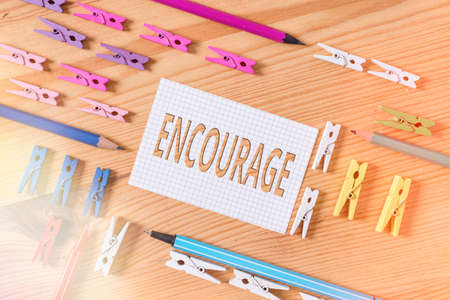 Conceptual hand writing showing Encourage. Concept meaning to inspire with courage, spirit, hope, spur on, or to persuade Colored crumpled papers wooden floor background clothespin