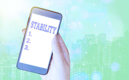 Writing note showing Stability. Business concept for property of a body that causes it when disturbed from equilibrium Modern gadgets white screen under colorful bokeh background